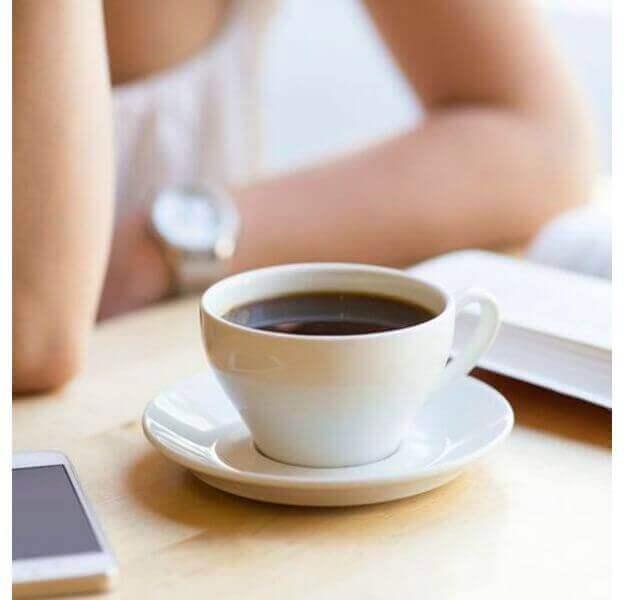 Kvinna med en kopp kaffe och sin telefon.