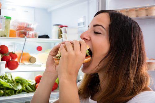 Kvinna som äter burgare.