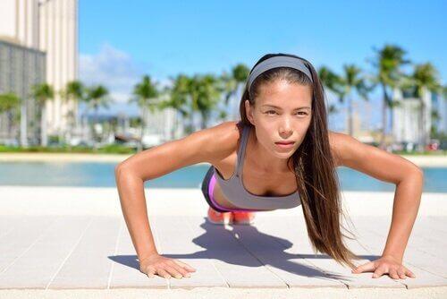 Kvinna som gör pressup för att tona ryggmusklerna.