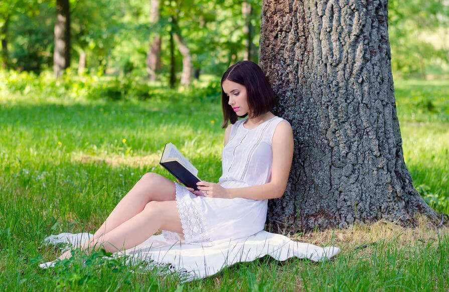 Kvinna som läser vid ett träd.
