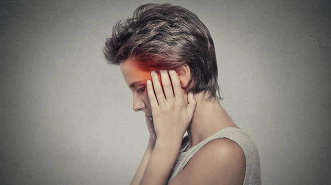 Kvinna som lider av huvudvärk.