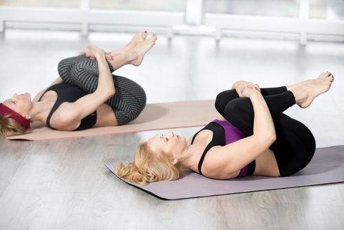 Kvinnor som utför övningar på matta.