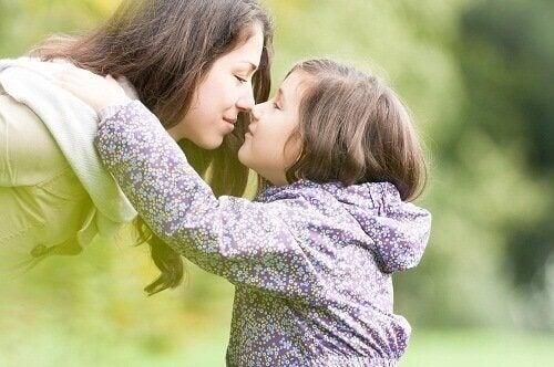 Mamma som nosar på dotter.