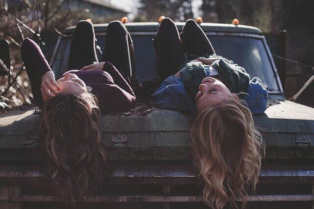 Tjejer som ligger på en bil.