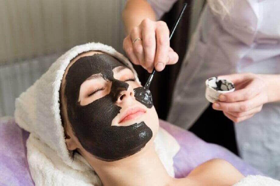 Applicering av svart ansiktsmask för att bli av med finnar