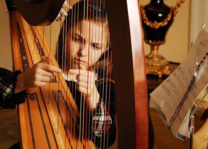 Flicka som spelar harpa.
