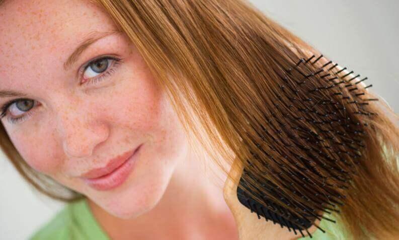 Kvinna som borstar håret.