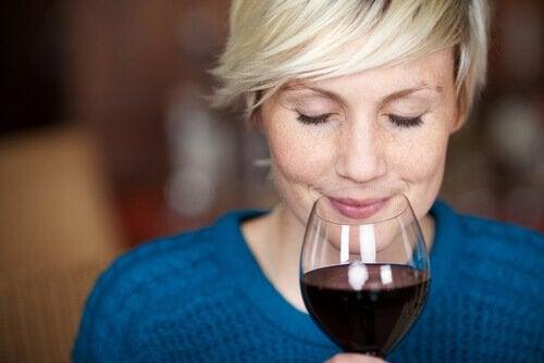 Kvinna som luktar på ett glas rödvin.