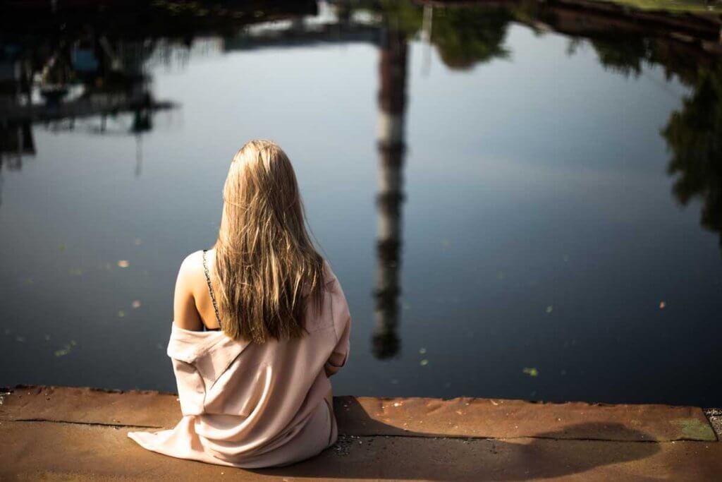Kvinna som sitter vid damm.