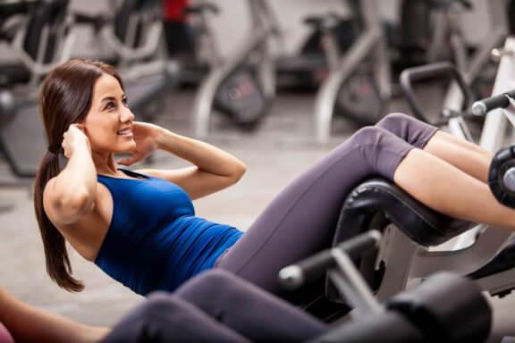 Kvinna som gör situps på gymmet.