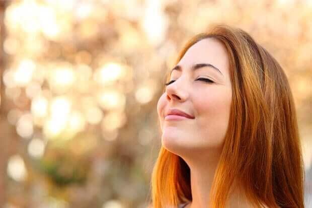 Kvinna som ser glad ut i solen.