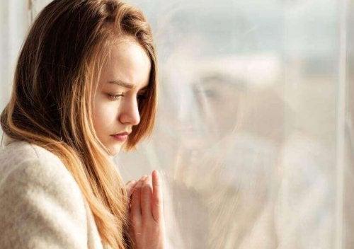 Kvinna som står vid fönstret.