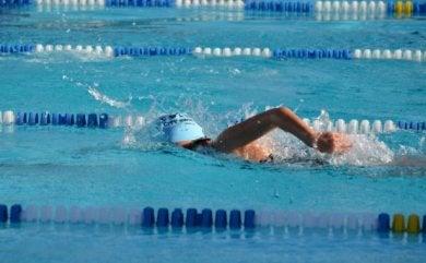 Person som simmar i bassäng.