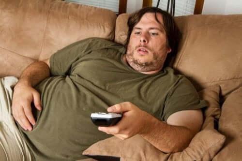 Man som ligger i soffan.