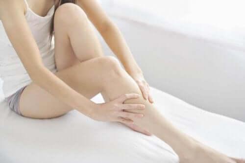 Kvinna som masserar ben.