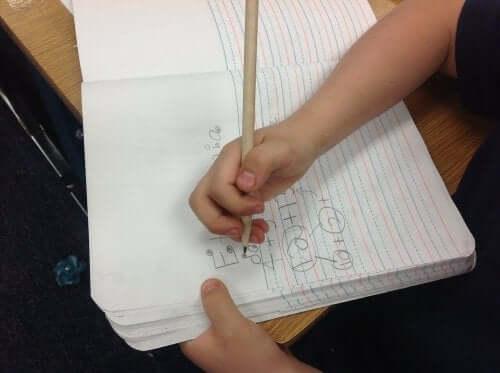 Barn skriver i bok
