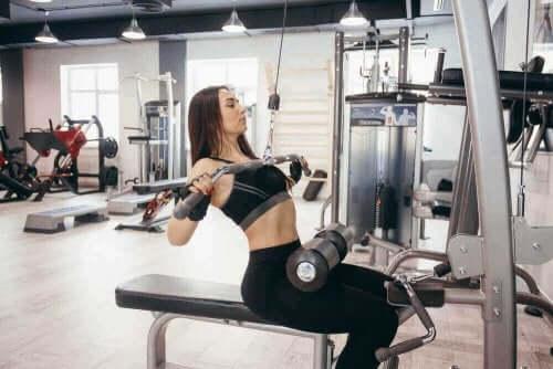 Kvinna styrketränar på gym
