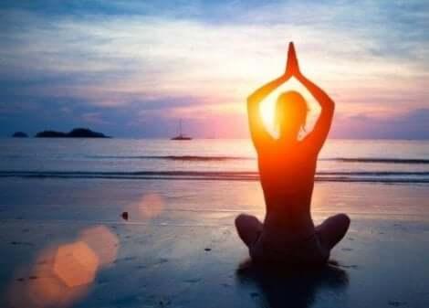 Person utövar yoga på stranden
