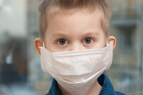 Barn har på sig ansiktsmask för att undvika att röra munnen.
