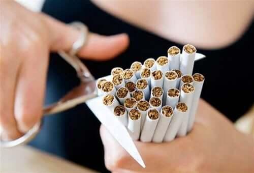 person klipper av ett paket med cigaretter