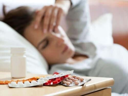 Kvinna med piller på sängbordet.