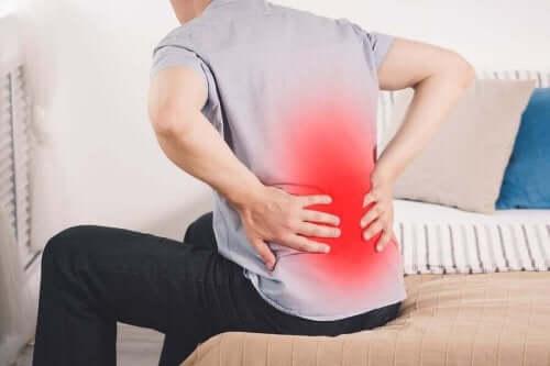 En person med strålande njursmärta håller sig för ryggen.