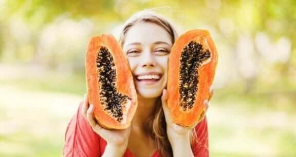 Kvinna håller upp en halvad papaya.