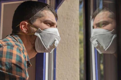 Man med mask tittar ut genom fönstret.