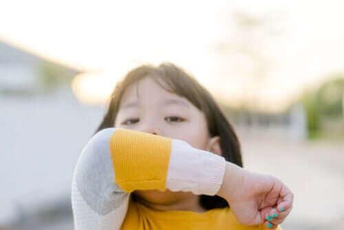 Barn hostar i armbågen.