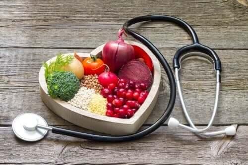 Nyttiga livsmedel efter en hjärtattack i en hjärtformad skål, med ett stetoskop bredvid.