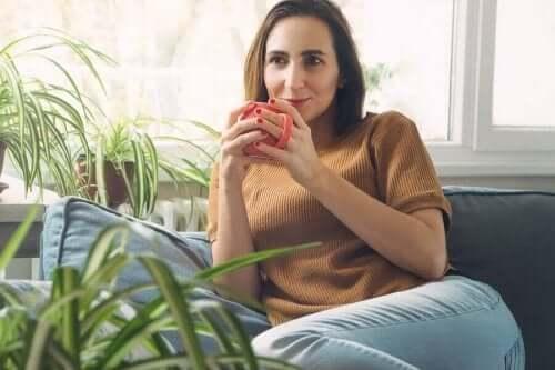 Kvinna lägger bort mobilen och njuter av sitt morgonkaffe.