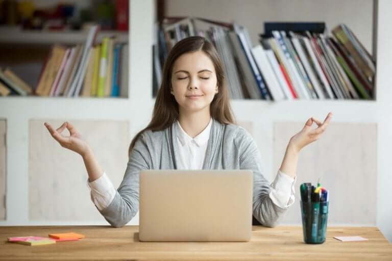 Kvinna mediterar på kontoret.
