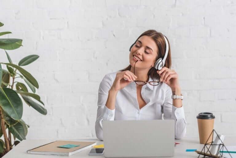 Kvinna sitter vid dator och arbetar hemifrån.