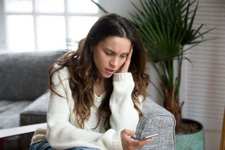 Oroad kvinna tittar på sin telefon.