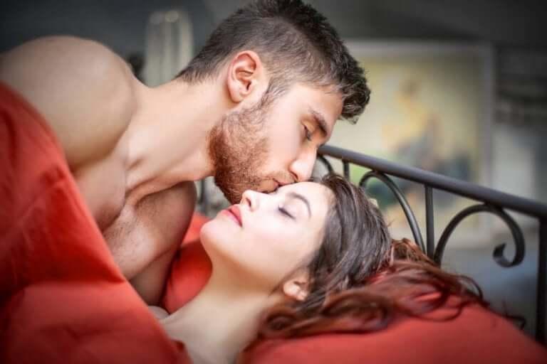 Man pussar en kvinna sensuellt på pannan.