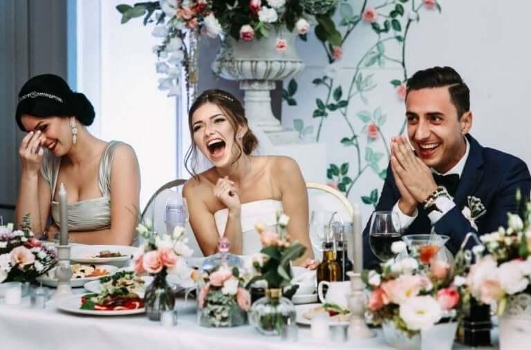 Brud och brudgum skrattar under bröllopsfesten.