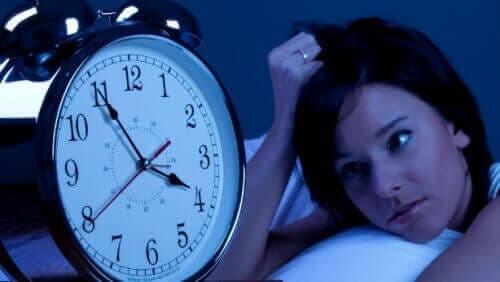 vaken kvinna i säng bredvid väckarklocka