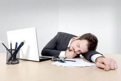en man som sover vid sitt skrivbord