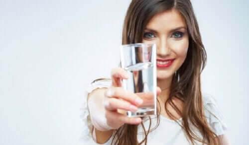 interstitiell cystit: kvinna håller upp vattenglas