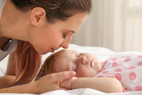 Skallasymmetri: mamma kysser sovande baby