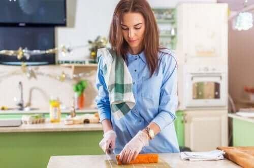 Listeria under graviditet: En gravid kvinna skär grönsaker i köket.