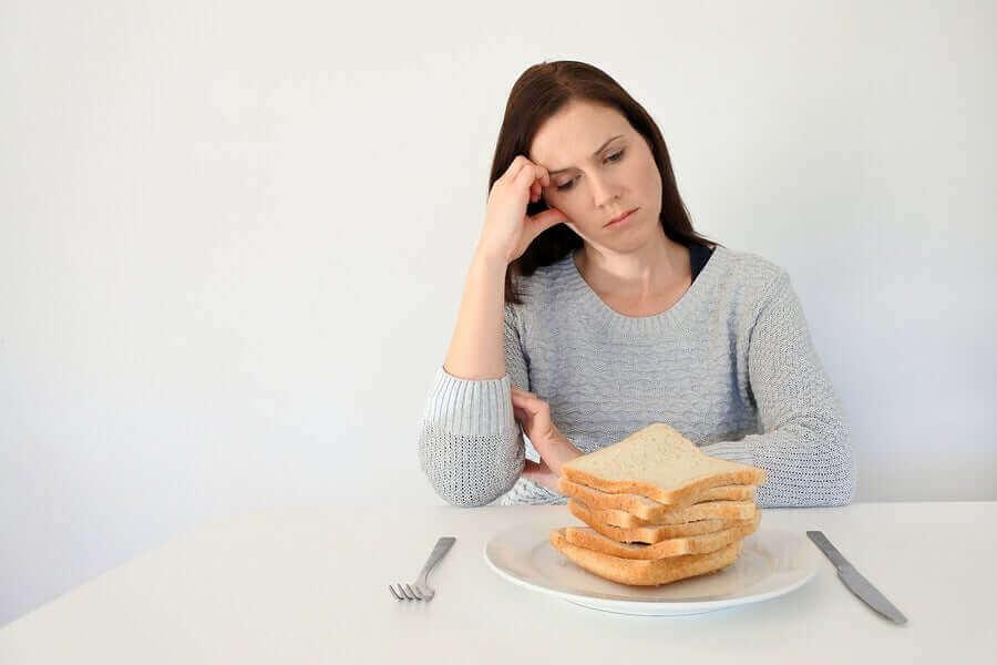 Glutenintolerant kvinna tittar ledset på en hög vetebröd.