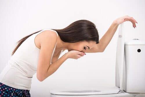 Kvinna spyr i en toalett.