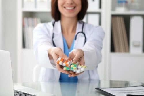 En läkare håller fram olika piller för en blödning efter operation