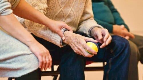 Kvinna håller handen på en man medan han använder en stressboll.