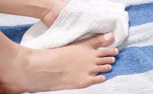 nageltrång: person torkar fötterna