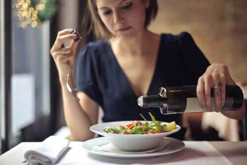 hoppa över middagen: kvinna häller olja på sallad