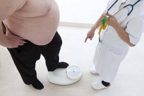 överviktig person väger sig hos läkare