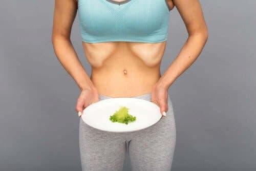 mager kvinna med tallrik som har diabetes och bulimi