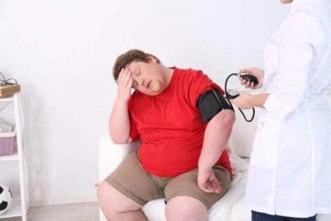 sårbara för värme: överviktig person ser varm ut under läkarundersökning